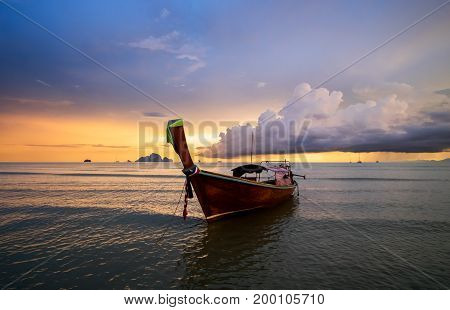 Traditional thai long tail boat on the sunset with colorful cloudy sky on background. Andaman Sea Krabi Province of Thailand.