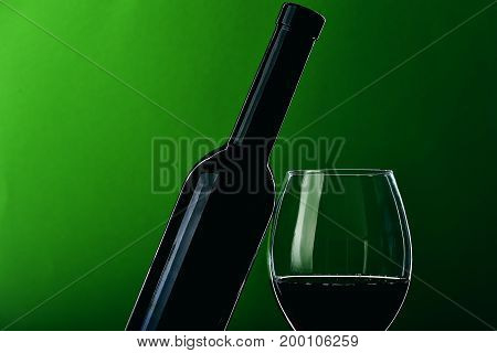Glass With Wine And Sloped Dark Bottle