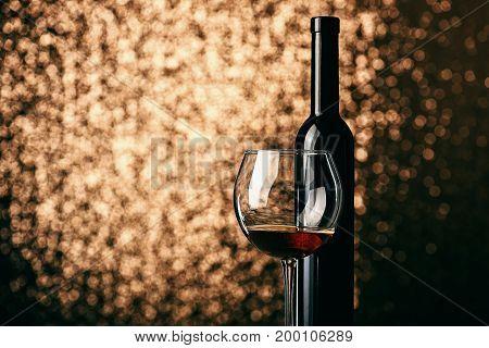 Alcohol Beverage In Glass Near Wine Bottle