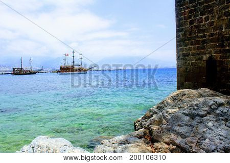 View from the rocky shore to the pleasure boats sailing at anchor in the city harbor (Alanya, Turkey).