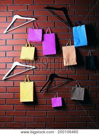 Colorful Shopping Bag And Wardrobe Hanger On Brown Brick Wall