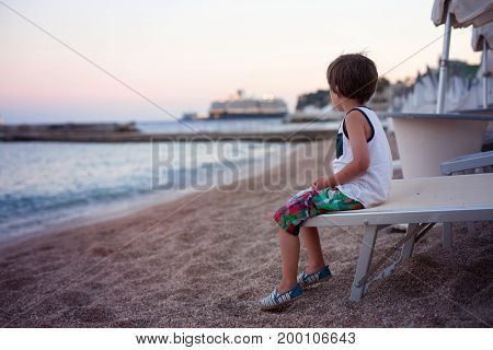 Portrait Of Cute Child, Boy, Contemplating The Beach On Sunset