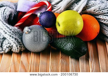 set of various fruits: lemon apple orange avocado with striped caramel candie scarf christmas balls on wooden studio background side view