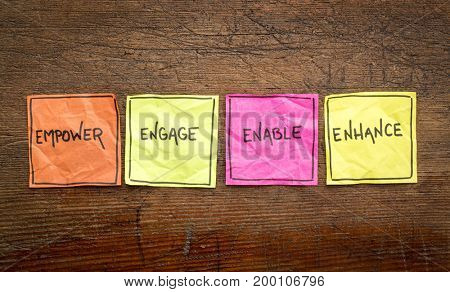 empower, engage, enable, and enhance inspirational concept - handwriting on isolated sticky notes against rustic wood