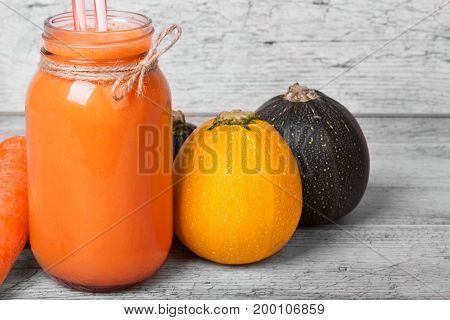 A wooden table with bright yellow and dark green zucchinis, wholesome carrot smoothie in a mason jar and a peeled carrot on a light wooden blurred background.