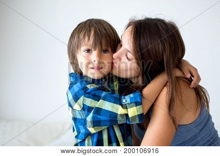 Portrait Of Beautiful Pregnant Mother With Love Hugging Her Precious Son In The Park