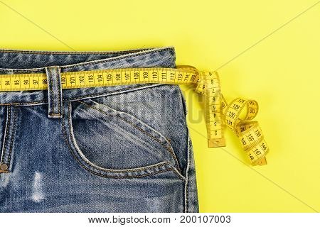 Upper part of denim trousers isolated on yellow background. Healthy lifestyle and dieting concept. Close up jeans with measure tape around waist. Blue jeans with yellow measure tape instead of belt.