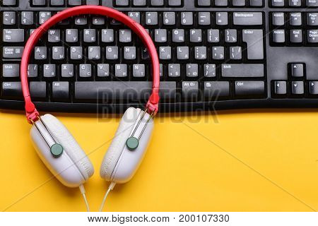 Earphones In Red And White With Computer Keyboard