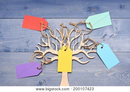 Beauty and shopping concept. Earring holder with price tags in several colours close up. Decorative tree to store jewellery. Organizer for jewellery made of wood on dark blue vintage background.