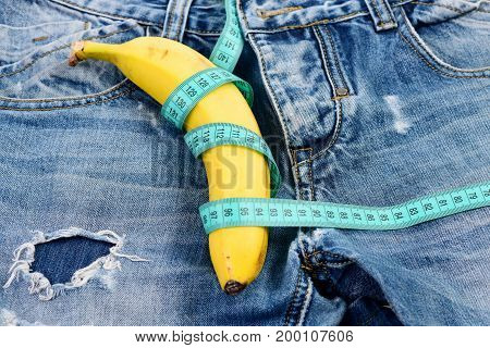 Jeans zipper and pocket close up. Mens denim pants crotch with banana imitating male genitals. Banana wrapped with blue measure tape on jeans selective focus. Health and male sexuality concept.