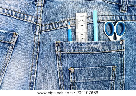 Engineers tools with denim fabric. Things for drawing in back pocket of male denim pants close up. Engineering and design concept. Metal scissors ruler blue pen and pencil in jeans pocket.