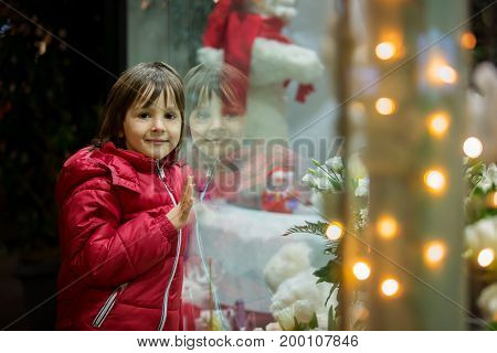 Cute Little Child, Boy, Watching Christmas Decoration With Toys In A Shop Window Display
