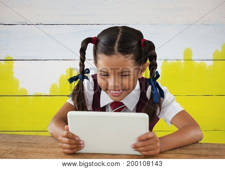 Digital composite of Girl on tablet in front yellow painted background