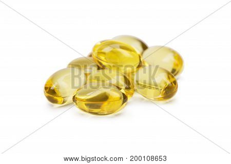 Fish oil capsules with omega 3 and vitamin D on white background. A heap of pils, tablets, drugs, medicaments, isolated on a white background. Transparent tablets with reflection, close-up.