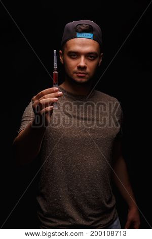 A drug addicted fellow holds a syringe in his hand on a dark black background, concept, drug addiction, injectable drugs, equipment for injecting drugs.