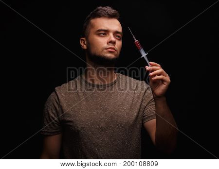 A drug addicted guy holds a syringe in a hand and isn't sure whether take it or not on a dark background, concept, drug addiction, injected drugs, addicted.