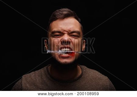 A drug user with addiction clamps a syringe between teeth on a dark black background, concept, drug addiction, injectable drugs, addicted, narcotics.