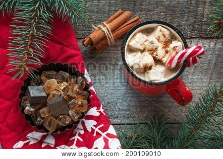 Christmas tradition drink. Cup of black coffee with marshmallow candy cane on the wooden background. New Year. Holiday card. Rustic style. Top view and copy space.
