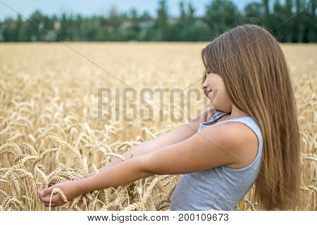 Portrait of adorable little girl with beautiful long hair touching wheat ears in the field on a summer day