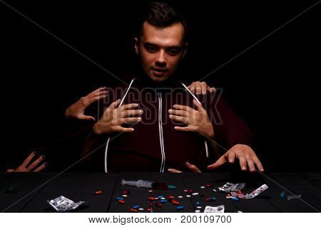 Women's hands coming from the dark seducing a stressed man to take a syringe with addictive, deadly drugs. A curious young man sitting next to an assortment of narcotics on the black background.