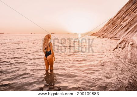 Blonde woman in black swimwear relax on quiet sea with warm sunset colors.