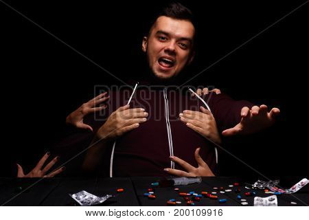 A narcomaniac freak in a red hoodie sitting next to many drugs: meth, marijuana, morphine, cocaine on the table. Hands instigating an affected young male to take narcotics on the black background.