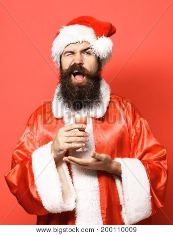 handsome bearded santa claus man with long beard on smilingface holding glass of alcoholic shot on hand in christmas or xmas sweater and new year hat on red studio background