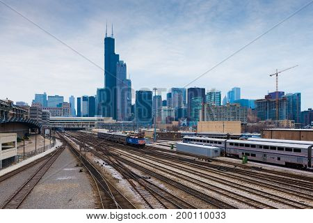 Chicago - March 2017, IL, USA: Chicago skyline at cloudy day. View from Roosevelt rd. on railroad tracks with trains and office buildings in downtown