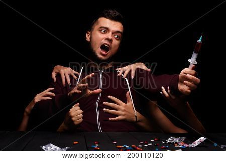 A handsome young student screaming, suffering from deadly drug cravings on the black background. A hallucinating addict sitting next to a table with various colorful drugs in tablets and capsules.