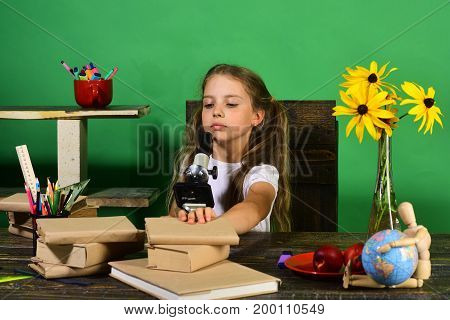 Girl Sits At Desk With Microscope, Stationery, Books And Flowers