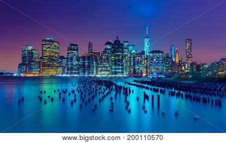 New York City at night. Manhattan skyline. Skyscrapers reflected in water. NY, USA