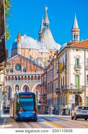 Padova (Padua) - February 2017, Italy: The street of Padua with traffic. Modern tram is moving towards the central square. The Basilica of St. Anthony of Padua (Basilica di Sant'Antonio di Padova)