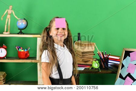 Schoolgirl With Happy Face And Pink Sticky Note On Forehead