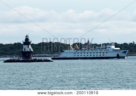 Orient Point New York USA - 27 July 2017: The Mary Ellen ferry ship is passing the Orient Point Lighthouse while transporting people and cars from New London Connecticut to Orient Point Long Island.