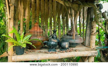 Ancient pottery pot for drinking water in Northern Thailand on the bamboo shelf