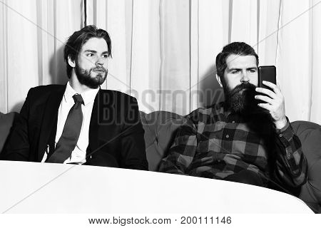 bearded men businessmen long beard brutal caucasian hipster with moustache hold mobile or cell phone has serious face unshaven guys with stylish hair in suit red tie and checkered shirt