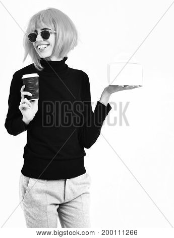 cute fashionable sexy woman or pretty young smiling happy girl in pink wig and fashion glasses holding coffee cup and meal box isolated on white studio background
