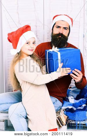 cute smiling blonde girl in beige dress take big blue present or gift from handsome bearded man with long beard in christmas red hat on white studio background