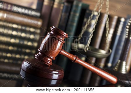 Gavel, books, scales on wooden background. Law concept. Place for text.