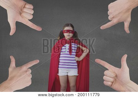 Digital composite of Hands pointing at girl in a super heroine custom against grey background