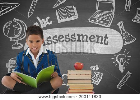 Digital composite of Happy student boy at table reading against grey blackboard with assessment text and education and sc