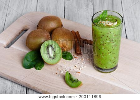 A top view of kiwi fruits full of nutritious vitamins, cinnamon sticks and walnuts on a cutting board and on a gray wooden background. An organic green smoothie from juicy kiwi, grated nuts, and mint.