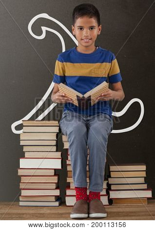 Digital composite of Student boy on a table reading against grey blackboard with school and education graphic