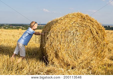 Boy pushes a bale of hay in the field