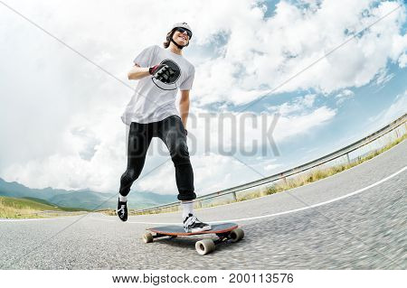A guy in a helmet and sunglasses accelerates pushing his foot on his longboard on a country road asphalt and smiles. Wide angle
