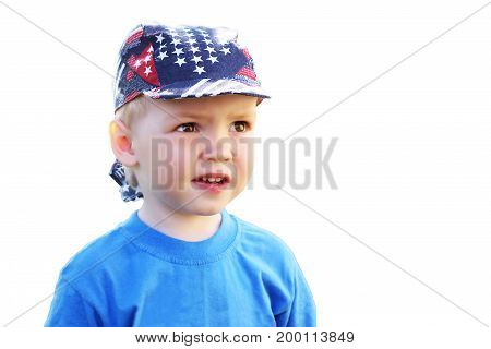 A young child in a cap laughs happily