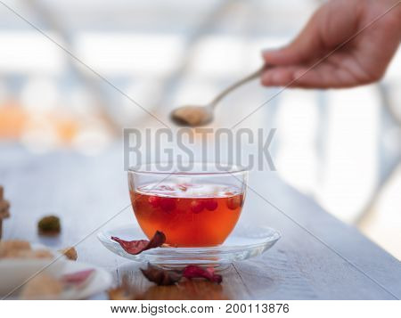 Close-up of a woman's hand with a spoon of sugar and a full teacup. Red tea in a cup with a spoon on a on a light blurred background. Tea with berries and leaves for a cafe breakfast. Copy space.