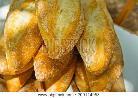 Pile of freshly baked rustic French baguettes stacked on garden table outdoor picnic preparation. Summer sunlight flecks lifestyle
