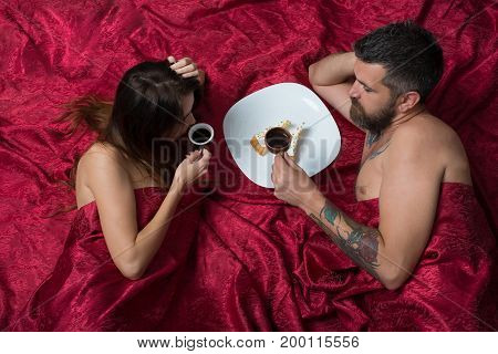 Couple in love lies on burgundy sheets. Love and sex concept. Man with beard having morning coffee and cake with pretty lady in bed top view. Man and woman with half covered bodies.