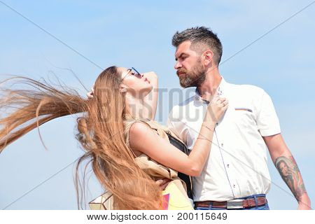 Man with beard and woman with messy long hair waving on wind. Couple holds packets on blue sky background. Sexy girl and guy with serene face expressions hug each other. Relationship and love concept
